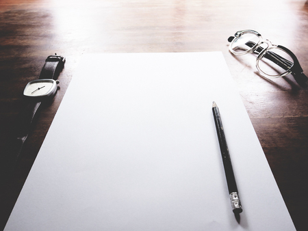 This is office equipment in minimal style, The picture of pen, glasses,paper and watch on wooden table. soft tone color, minimal style