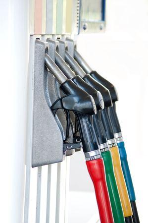 A row of petrol pump nozzles at a garage.