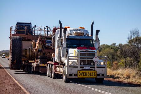 Foto de KARIJINI - WESTERN AUSTRALIA - JULY 11, 2018: The Western Star road train with Oversize sign and extremely wide dumper truck on an asphalt road in Western Australia near Karijini National Park. - Imagen libre de derechos