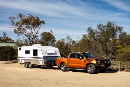 Foto de Off road pickup car with air intakes and a white caravan trailer in Western Australia prepared for an adventure. - Imagen libre de derechos
