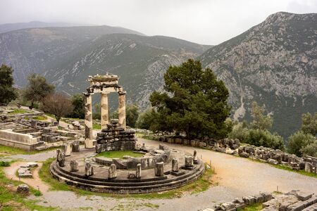Photo for Tholos of Delphi (Athena Pronaia Temple) as one of many ruins in complex in Delphi, Greece with slight mist because of overcast weather - Royalty Free Image