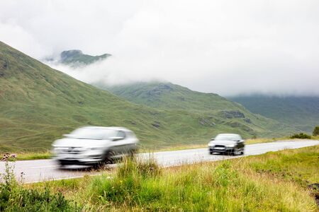 Photo for Two cars driving on a road in the landscape of Scottish Highlands in misty weather with motion blur effect increasing the impression of speed - Royalty Free Image