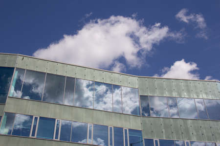 Photo for Reflections of the sky and clouds on a modern facade of a building on a summer day - Royalty Free Image