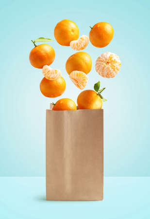 Foto de Flying tangerines, recyclable paper bag, isolated from the blue background - Imagen libre de derechos