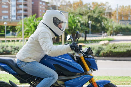 Photo pour Woman driving a motorcycle through the city - image libre de droit