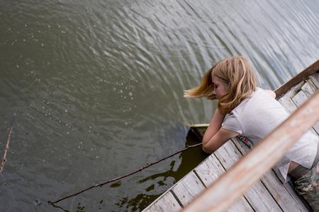 Foto de Teen girl lying on her stomach on a wooden bridge near the river - Imagen libre de derechos
