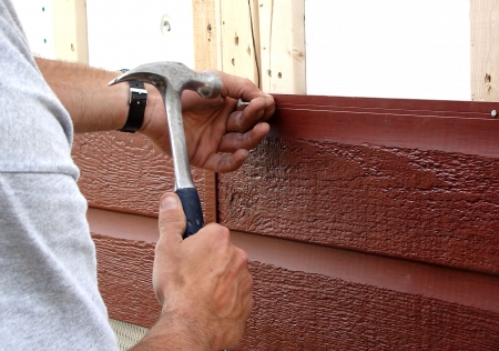 Action shot of a construction worker hammering a nail to put up new siding during major house renovations.