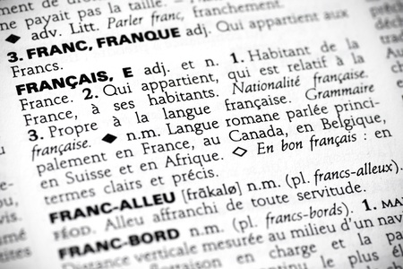 Macro shot with focus on the word franᅵais and its definition in a french dictionary.