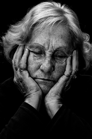 In a dark place: Dramatic exagerated low key portrait of an elderly woman looking very depressed and alone.