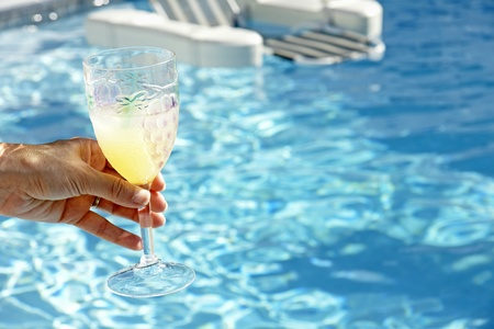 Join the fun and relaxation: woman's hand handing over a refreshing cocktail to be drank in the beautiful pool water