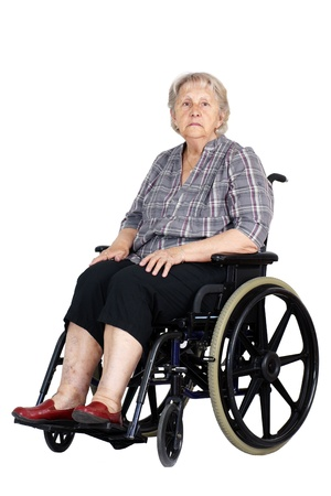Sad or depressed senior woman in a wheelchair, looking down, studio shot isolated over white background.
