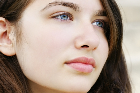Portrait of s beautiful hopeful or pensive young woman with fair skin and light blue and green eyes, simple and natural.