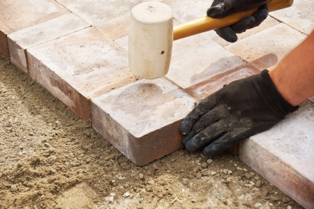Photo for Installing paver bricks on patio, mallet to level the stones - Royalty Free Image