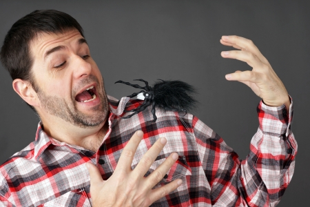 Prank or arachnaphobia concept: man scared by fake plastic spider on shoulder