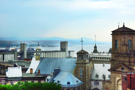 Old Quebec city skline with tin rooftops and chruches, St.Lawrence river and bridge in the background.