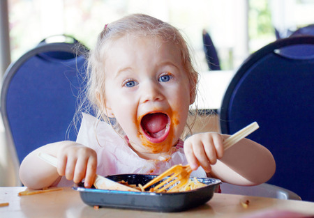 Photo for Funny little blond girl eating pasta and making a mess - Royalty Free Image