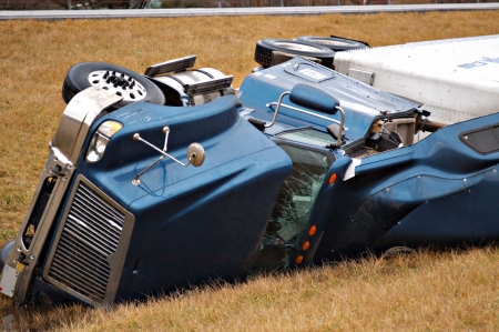 Photo pour A tractor trailer on its side in the median after a roll over accident.  - image libre de droit