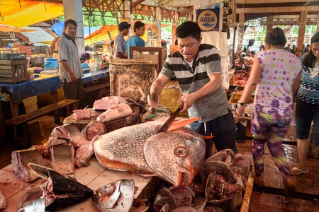 Photo for Tomohon, Indonesia - Dec 23, 2015: Indonesian man cuts the big fish on Tomohon Traditional Market. North Sulawesi - Royalty Free Image