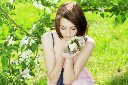 The image of a beautiful girl on a background of flowering treesの写真素材