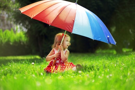 The image of a little girl with a rainbow umbrella in parkの写真素材