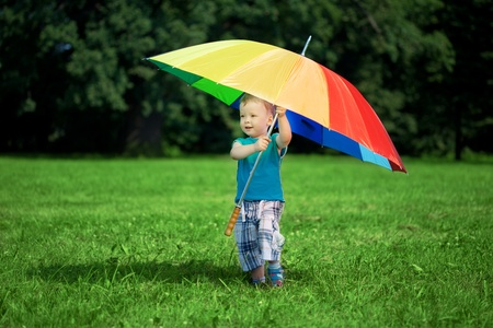 The image of a little boy with a big rainbow umbrellaの写真素材