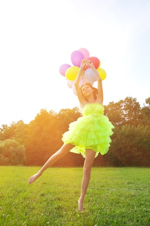 Bright happy woman holding bunch of colorful air balloons