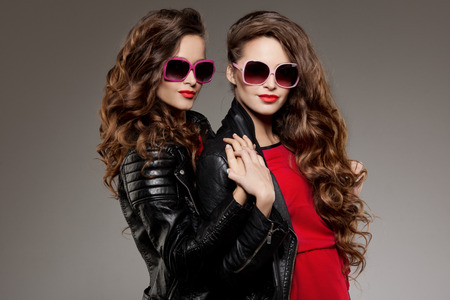 Sisters twins in hipster sun glasses laughing Two fashion models Women smiling positive Friends group having fun, talking Youthful friendship youth adults people culture concept Young girls rock party
