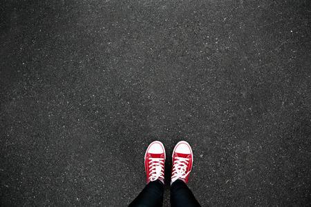 Foto de Gumshoes on urban grunge background of asphalt. Conceptual image of legs in boots on city street. Feet shoes walking in outdoor. Youth Selphie Modern hipster - Imagen libre de derechos