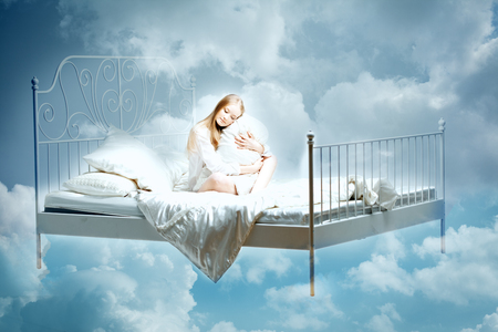 Sleeping woman. Girl with a pillow and blanket on the bed among the clouds in dreams