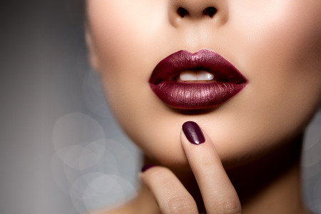 Foto de Red woman lips close up. Beautiful model girl with lipstick, manicure with nail polish Products Treatment - Imagen libre de derechos