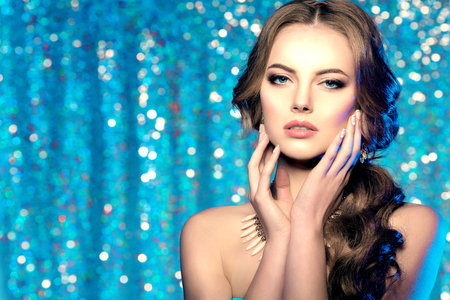 Foto de Winter woman model gorgeous beauty makeup stylish hairstyle. Young girl on the background bokeh. Lady make up Mascara for long lashes lipstick on lips eye shadow shiny hair manicure with nail polish Products Treatment - Imagen libre de derechos