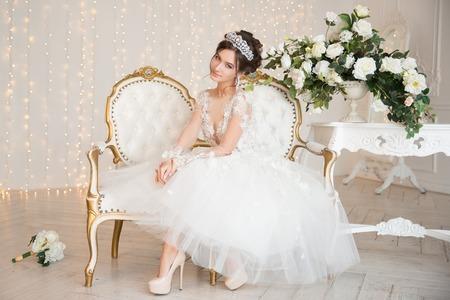 Foto de The bride in a short dress with lace in the crown earrings. - Imagen libre de derechos