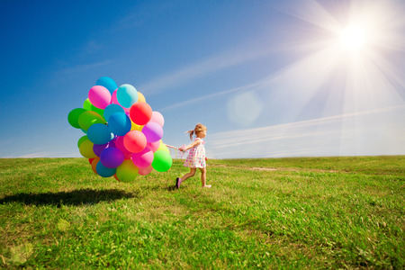 Photo pour Happy little girl holding colorful balloons on a green meadow. - image libre de droit