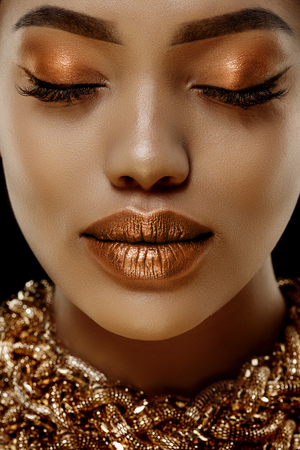 Photo pour Gold Luxury black skin woman African Ethnic female face. Young african american model with jewelry - image libre de droit