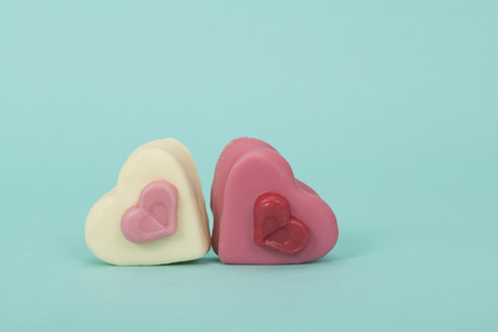 Two heart sheaped pink petit four candy's on a turquoise background