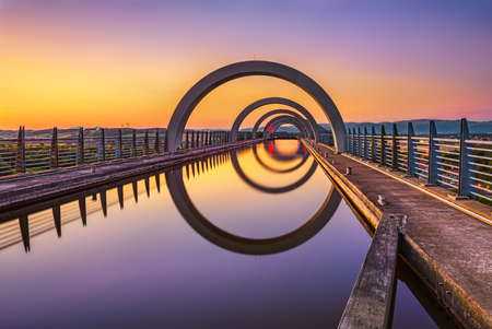 Photo pour Falkirk Wheel at sunset. Falkirk Wheel is a rotating boat lift in Scotland and connects the Forth and Clyde Canal with the Union Canal. Long exposure. - image libre de droit