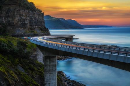 Photo pour Sunset over the Sea cliff bridge along Australian Pacific ocean coast with lights of passing cars near Sydney, Australia. Long exposure. - image libre de droit