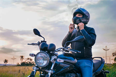 Photo pour Man sitting on a motorcycle, wearing jeans and a black jacket, fastening his helmet with a landscape in the background. - image libre de droit