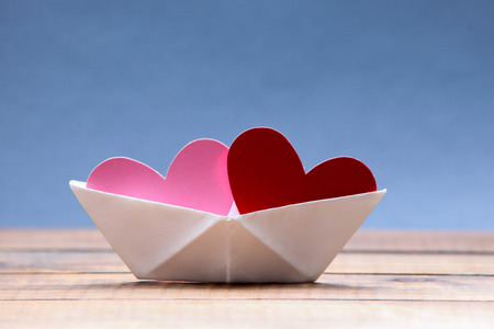 Photo pour Paper hearts inside paper boat with blue background - image libre de droit