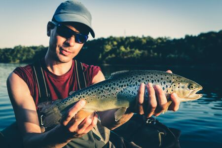 Photo pour Fisherman with catch of big Brown Trout on lake in Jesenice, Slovenia. Sunny summer day. Still water fly fishing and outdoor lifestyle theme. - image libre de droit