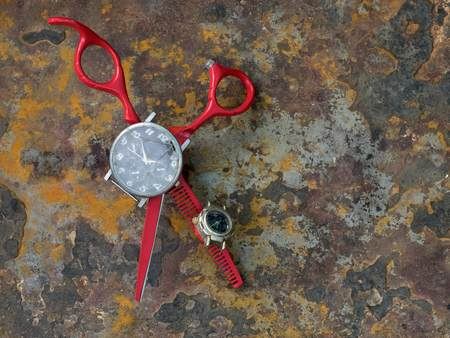 Red stylish hairdresser scissors with graceful handles on rusty background, in the middle of the instrument lie a black wristwatch with broken glass.