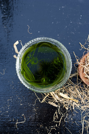 Dark green colored Khus or vetiver grass's extracted syrup on wooden surface with some dried vetiver grass used in Indian and Asian summer drinks as well as cold drinks.;