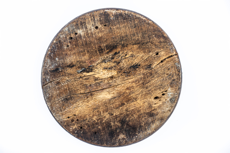 Close up of brown colored textured circular wooden piece isolated on white.