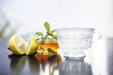 Photo pour Close up of honey tea isolated on wooden surface i.e. Honey,lemon juice, water, ginger and some mint leaves all mixed together in a transparent glass cup. - image libre de droit