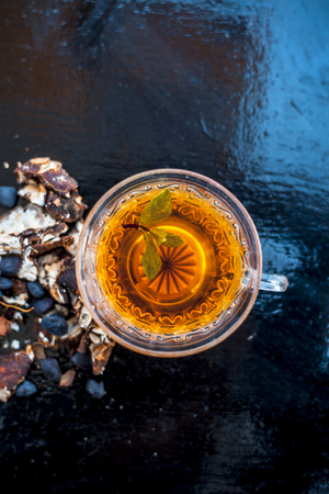 Tamarind or imli or amli in a clay bowl along with its roasted seeds and extract tea in a transparent glass cup with mint or mentha leaves on top on wooden surface.