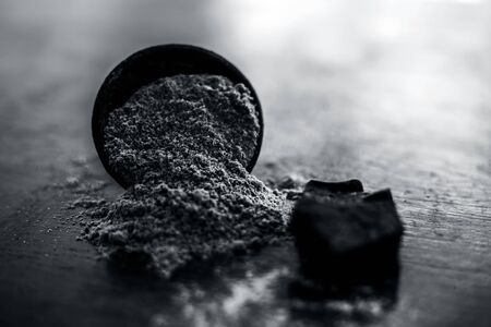Raw organic hing or devil's dung or Asafoetida on wooden surface along with its powder in a black colored clay bowl and some mint leaves or mentha leaves on it.