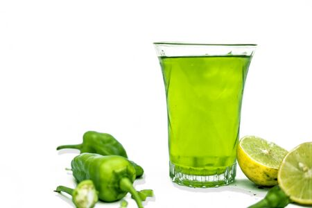 Close up shot of raw cut chilies with some sliced lemons isolated on white along with its chili flavored drink with it in a glass. Horizontal shot with copy space.Idle for advertisement purposes.