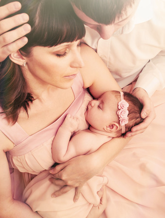 caring loving parents holding cute sleeping little baby girl with tenderness family relationship