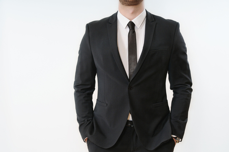 close up part of business man body in black suit with hands in pockets on white background; business concept
