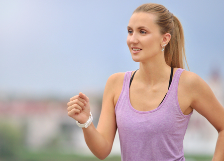 Fitness young woman jogging in the city park. Fitness girl training outdoor. Close up portrait.